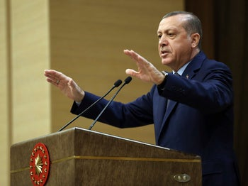 Recep Tayyip Erdogan, in trademark dark blue suit, light colored shit and tie, standing at a dais, his arms raised to shoulder height as he talks: Dec. 14, 2016.