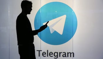 A man is seen as a silhouette as he checks a mobile device whilst standing against an illuminated wall bearing Telegram's logo, London, U.K., January 5, 2016.