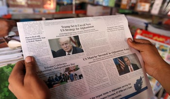 An Afghan man reads a local newspaper with photo of the U.S. President Donald Trump in Kabul, Afghanistan, Tuesday, Aug. 22, 2017.