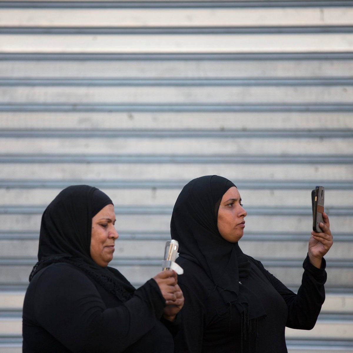 Israeli Arab women take pictures with their smartIsraeli Arab women take pictures with their smartphones during a parade for the Eid al-Adha festival in Jaffa, Sept. 12, 2016.