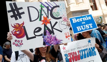 Demonstrators hold signs in Philadelphia, Pennsylvania on the first day of the Democratic National Convention on July 25, 2016.