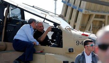 Prime Minister Benjamin Netanyahu sits inside an Apache Helicopter and speaks Israel Air Force chief Amir Eshel during his visit to the Tel Nof air force base in southern Israel, August 17, 2016.