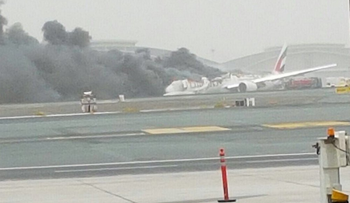 Black smoke emerges from a plane after crash-landing at Dubai International Airport, August 3, 2016.