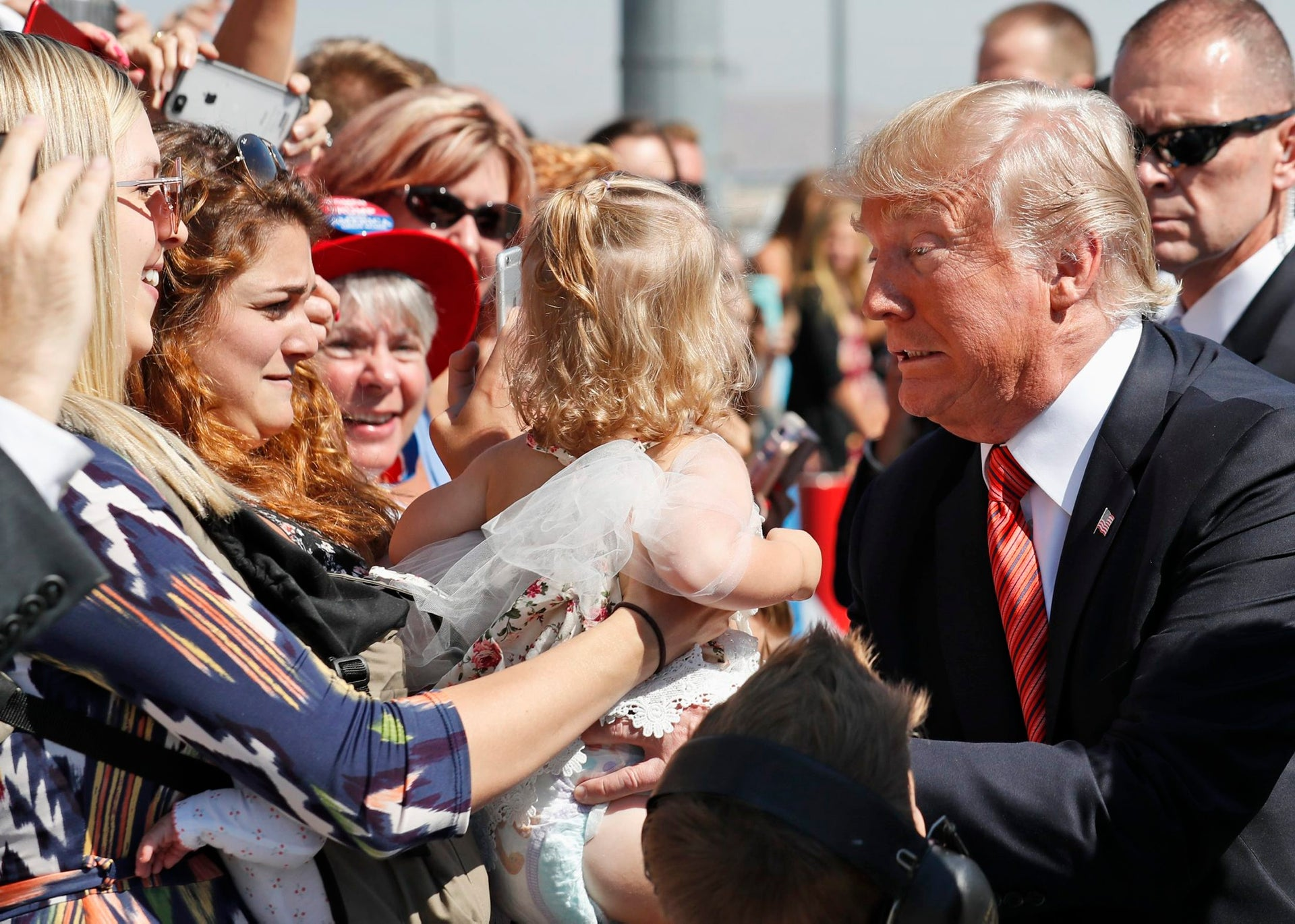 President Donald Trump struggles to hold a baby as he greets supporters as he arrives in Reno, Nev.,  Aug. 23, 2017.