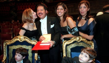 Nobel Laureate Ahmed Zewail shows his award with family members after the award ceremony in Stockholm on December 10, 1999.