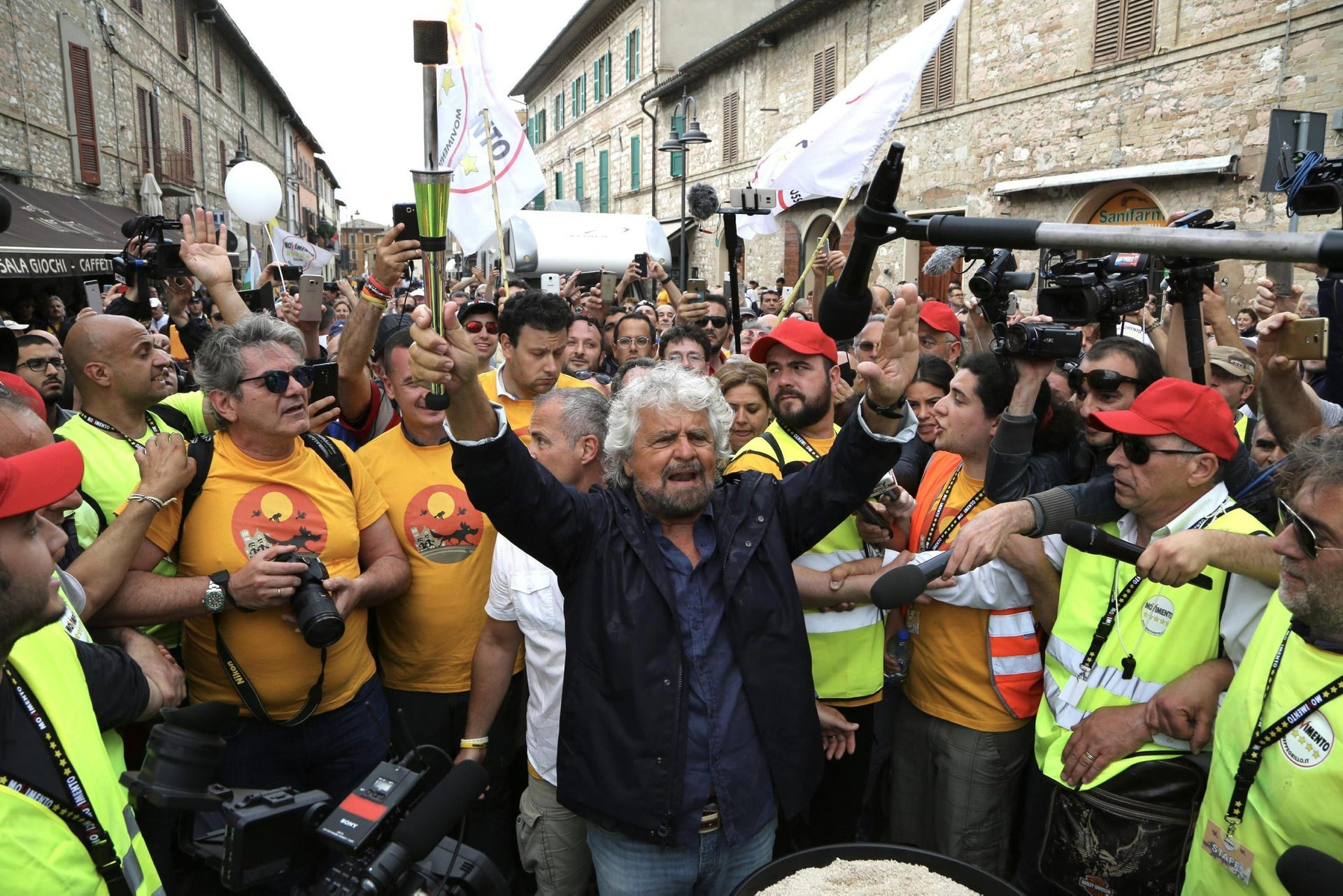 Italian Five Stars Movement's leader Beppe Grillo holds a torch as he takes part in a march from Perugia to Assisi, Italy, May 20, 2017.