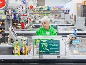 File photo: A woman serving a customer at the checkout of a Mega supermarket in Tel Aviv, January 2017.