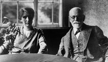 Sigmund Freud and daughter Anna sitting at a table.