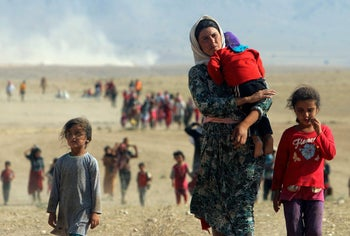 A Yazidi woman carrying a child fleeing violence from forces loyal to ISIS in Sinjar, Iraq on August 11, 2014.