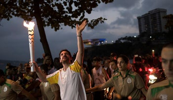 Leonardo Espindola carries the Olympic torch on its way to Rio de Janeiro for the opening ceremony of Rio's 2016 Summer Olympics, in Niteroi, Brazil, Tuesday, Aug. 2, 2016.