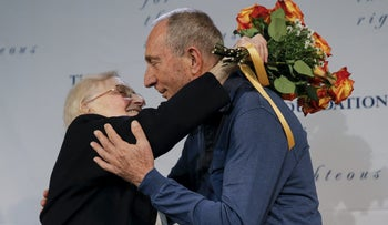 Rescuer Krystyna Jakubowska (L) and holocaust survivor Michael Hochberg hug on stage during a ceremony after arriving from Israel at John F. Kennedy airport in the Brooklyn borough of New York December 2, 2015. Survivor Hochberg of Israel and rescuer, Jakubowska of Poland, have been brought back together by The Jewish Foundation for the Righteous.