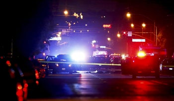 Police vehicles line the street around a vehicle in which two suspects were shot following a mass shooting in San Bernardino, California December 2, 2015.