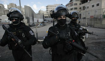 Three Israeli officers stand guard in the Shoafat refugee camp, ahead of the demolition of Ibrahim al-Akari's home, December 2, 2015.