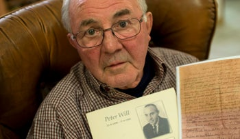 Joop Will holds a picture of his father Peter and a copy of the letter his father wrote during World War II as he poses for a portrait in Lelystad, Netherlands, November 13, 2015.