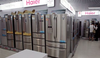 FILE PHOTO: Customers inspect Qingdao Haier Co. Ltd. refrigerators in Shanghai, China, on Monday, Aug. 10, 2009.