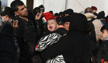A child cries as a large group of migrants and refugees wait to board a train after crossing the Greek-Macedonian border, December 1, 2015.