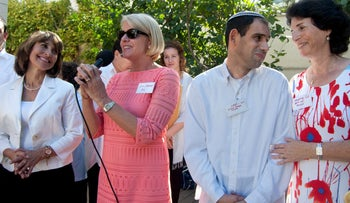 Choirmaster Elina Durian, host Jean Murphy holding a microphone as she addresses the crowd, Beit Uri resident Hezi and Beit Uri's Jeanette Koll at the Beit Uri event in Herzliya last Friday.