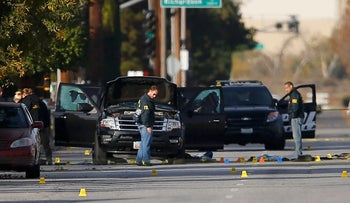 FBI and police continue their investigation around the area of the SUV vehicle where two suspects were shot by police following a mass shooting in San Bernardino, California December 3, 2015.