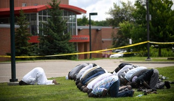 Mohamed Omar leads afternoon prayers outside the police tape surrounding the Dar Al Farooq Center Islamic Center after an early morning explosion on Saturday August 5, 2017 in Bloomington, Minnesota.