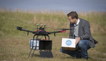 Maron Kristofersson, chief executive officer of Aha, removes a package from a drone manufactured by Flytrex in Reykjavםk, Iceland on Friday August 25, 2017.