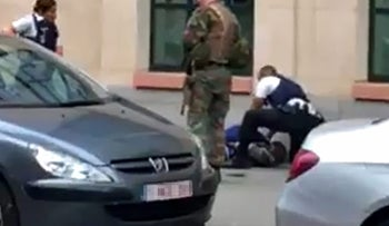 TOPSHOT - This screengrab shows police officials and a soldier looking at a man on the pavement in the city centre of Brussels on August 25, 2017, where a man is alleged to have attacked soldiers with a knife and was shot.  / AFP PHOTO / Belga / STR / Belgium OUT