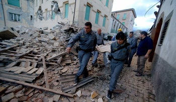Rescuers carry a man from the rubble after a strong earthquake hit Amatrice, Italy, August 24, 2016.