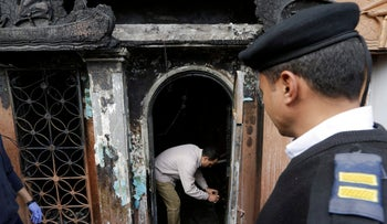 An Egyptian forensic member checks the gate of the nightclub which was attacked in Cairo, Egypt, Friday, Dec. 4, 2015.