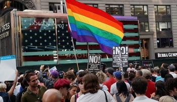 A rainbow flag flies as people protest Trump's plan to reinstate a ban on transgender people from serving in the U.S. military, New York City, July 26, 2017.