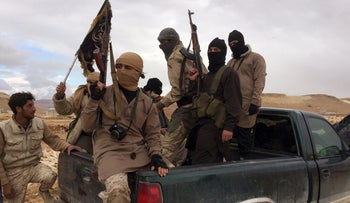 Al-Qaida-linked Nusra Front fighters carry their weapons on the back of a pick-up truck during a prisoner exchange in Arsal, Lebanon, December 1, 2015.