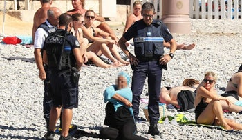 Police enforcing a ban on the burkini hovering by woman on Nice beach as she removes a tunic, August 24, 2016.
