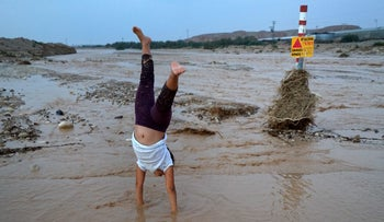 A child does a handstand in a flooded stream next to Ein Yahav in southern Israel, October 26, 2015.