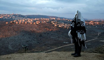A man prays in the illegal outpost of Amona in the West Bank, December 18, 2016.