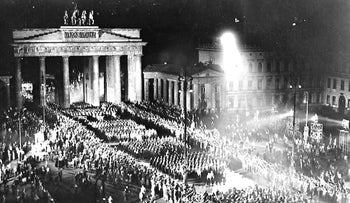 National Socialist troops with torches marching in Berlin to celebrate Hitler taking over the power on Jan. 30, 1933. In background the Brandenburg Gate.