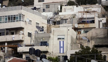 An Israeli flag hangs on the wall of a building that was taken over by Israeli settlers after Palestinian families were evicted in the East Jerusalem neighbourhood of Silwan.
