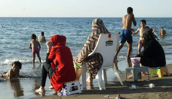 This file photo taken on August 3, 2016 shows Algerian families gathered on a public beach, reserved especially for families and their children, in the capital Algiers.