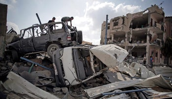 Palestinians atop a destroyed car in August 2014, in the Gaza town of Rafah, a site of heavy fighting in the two-month war.