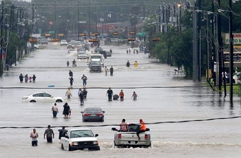 People walk through the flooded waters of Telephone Rd. in Houston on August 27, 2017