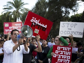 "Joint List MKs Dov Khenin, left, and Ayman Odeh, center, in anti-violence and pro-coexistence demonstration in Tel Aviv, Oct. 9, 2015. The placards in read, ""Jews and Arabs refuse to be enemies."""