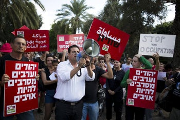 """Joint List MKs Dov Khenin, left, and Ayman Odeh, center, in anti-violence and pro-coexistence demonstration in Tel Aviv, Oct. 9, 2015. The placards in read, """"Jews and Arabs refuse to be enemies."""""""