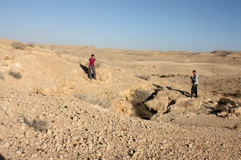 Archeaologists stand at the entrance to the Ashalim Cave in the Negev desert.