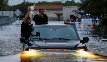 Residents use a truck to navigate through flood waters from Tropical Storm Harvey in Houston, Texas, U.S. August 27, 2017
