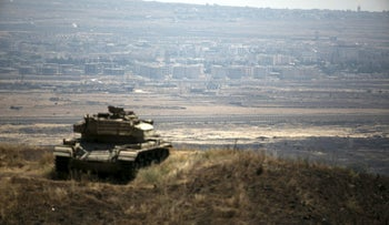 The Syrian area of Quneitra is seen in the background as an out-of-commission Israeli tank parks on a hill, near the ceasefire line between Israel and Syria, in the Israeli-occupied Golan Heights, August 21, 2015.