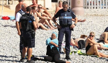 French police look on, making sure a female beach goer removes her modest clothing.