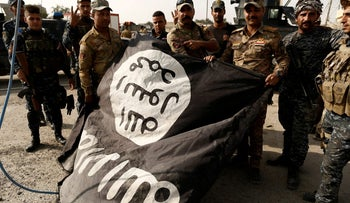 Iraqi soldiers pose with an Islamic State flag in the town of al-Shura near Mosul, October 30, 2016.