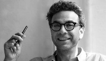 Stephen J. Dubner, reporter, with glasses and smiling, wearing button-down shirt with top button undone.