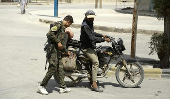 Kurdish police officers on a motorcycle in the Syrian city of Hasakeh on August 22, 2016.