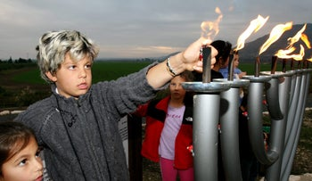 """Children, wearing sweaters to ward off the December chill, lighting Hanukkah """"candles"""", in this case gas-fired flares, at Hula Park. The origin of the custom to light fire to mark Hanukkah remains obscure - but may have originated with the Roman vassal king Herod."""