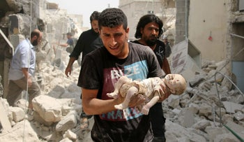 A Syrian man carries a dead baby after a barrel bomb attack on the Bab al-Nairab neighborhood of Aleppo on August 25, 2016.