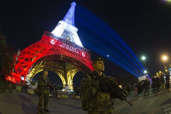 A French soldier enforcing the Vigipirate plan, France's national security alert system, stands in Paris in front of the Eiffel Tower, Nov. 18, 2015.
