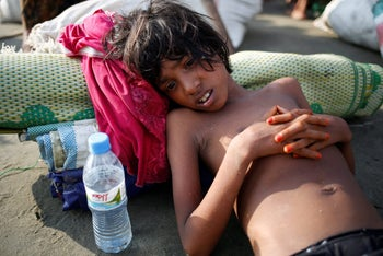 A Rohingya refugee girl lies on the ground as she suffers from dehydration after crossing the Bangladesh-Myanmar border by boat through the Bay of Bengal in Teknaf, Bangladesh, September 5, 2017.